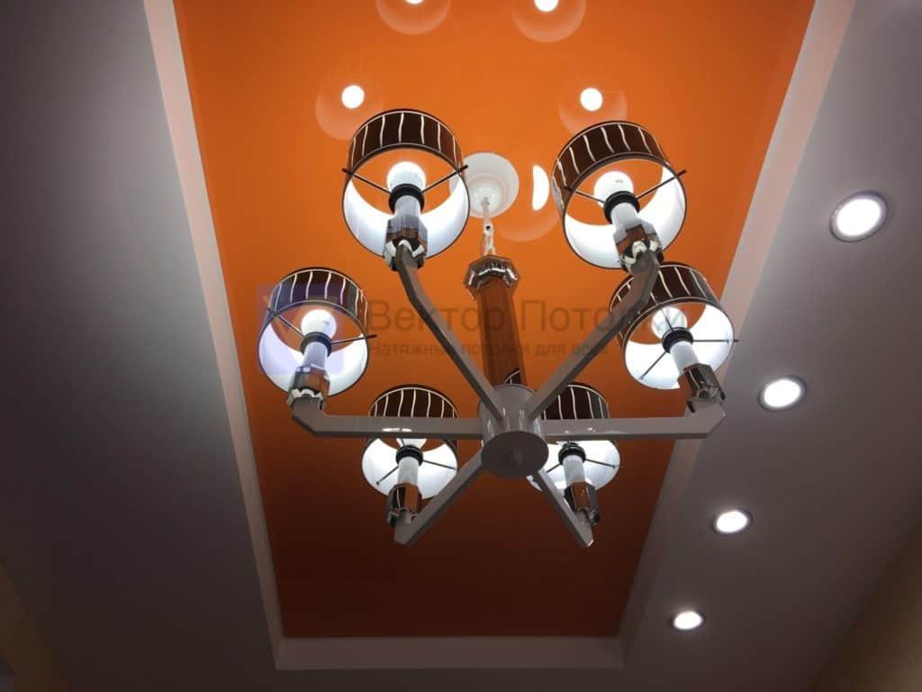 оранжевый натяжной потолок с люстрой и светильниками
